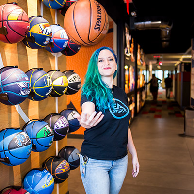 Female alumni with bright green hair juggling a basketball standing infront of NBA live basketball wall