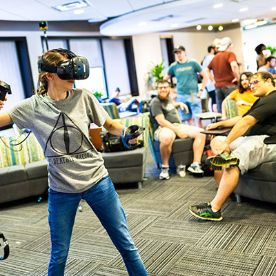 Young female student wearing VR gear playing in a large room with other students in the background