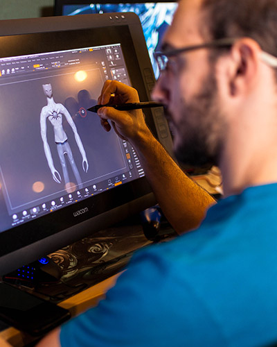 Young male student drawing on a 3D character large wacom display